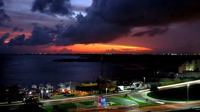 the_suns_last_orange_light_disappearing_on_the_horizon_behind_a_harbour_by_a_road.1920x1080